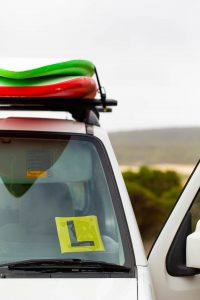 Photo of car with surfboards on roof rack and L plate on windscreen, photo by Caro Telfer Photographer